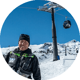 Man in the snow with alpine lifts